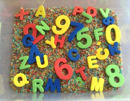 Teach your kids about letters and numbers in a sensory rice bin.