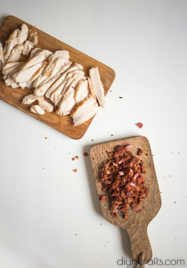 Preparing chicken breasts and bacon.