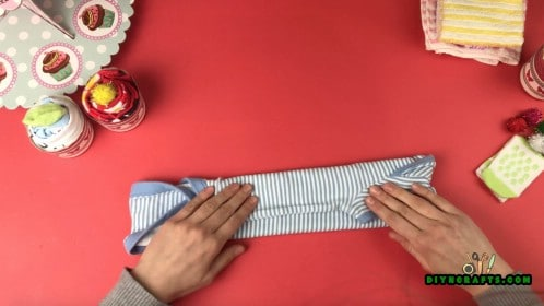 Start by folding the onesie (or washcloth) in thirds lengthwise.