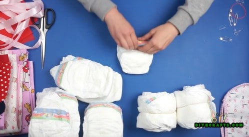 Roll 4 diapers into one another to create a wheel. Do this 6 times so you have 6 wheels.