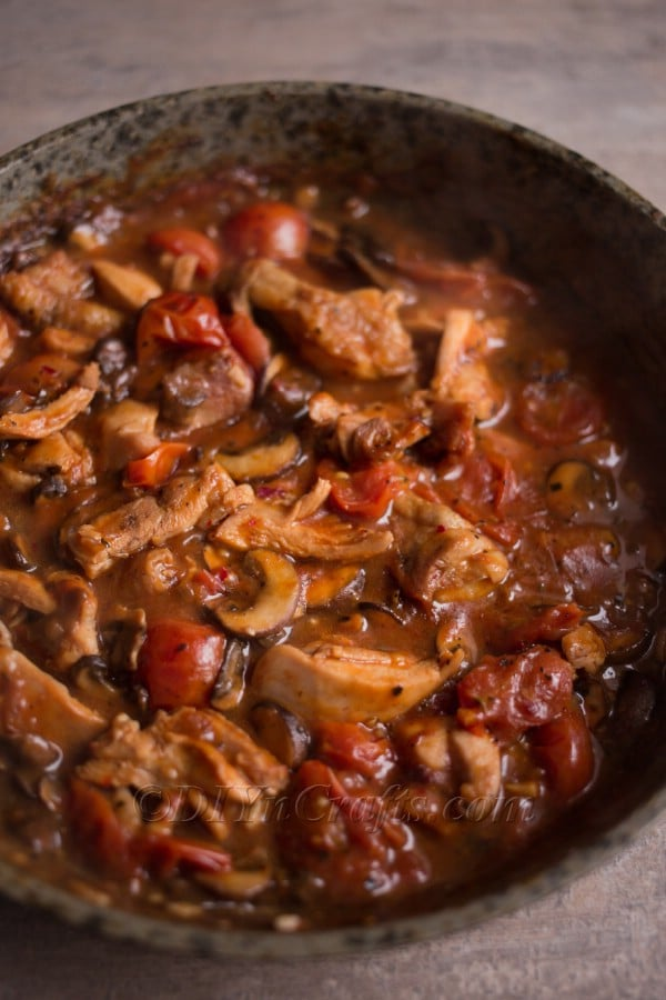 Mixing chicken, mushrooms and sauce.